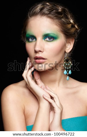 portrait of beautiful young woman with green and blue eye shade make up touching her face