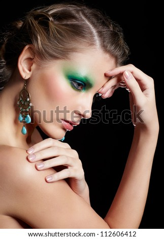 portrait of beautiful young woman with green and blue eye shade make-up touching her shoulder and forehead - stock photo