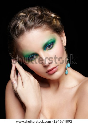 portrait of beautiful young woman with green and blue eye shade makeup posing on black