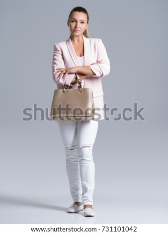 Portrait of beautiful young  woman with handbag. Fashionable trendy female posing at studio.