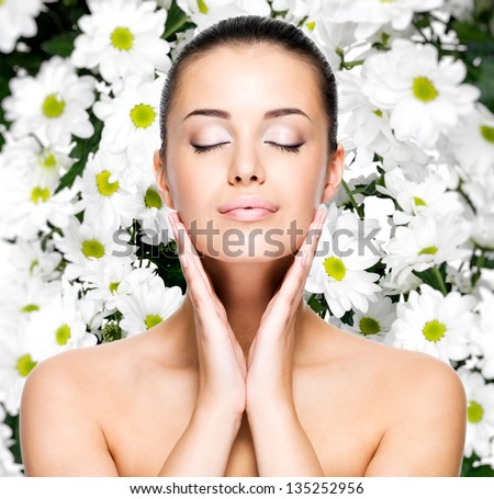 Portrait of beautiful young woman with healthy skin of face over flowers background . Beauty treatment concept
