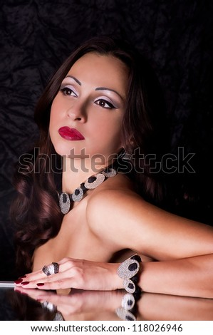 Portrait of beautiful young woman with jewelry on black background - stock photo