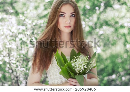 Portrait of beautiful young woman with lily of the valley. Girl on nature. Spring flowers. Fashion beauty - stock photo