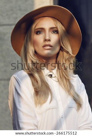 Portrait of beautiful young woman with long blond hair wearing big hat and white shirt. Over her body is small shadow. - stock photo