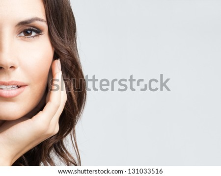 Portrait of beautiful young woman with long curly hair, over grey background, with copyspace - stock photo