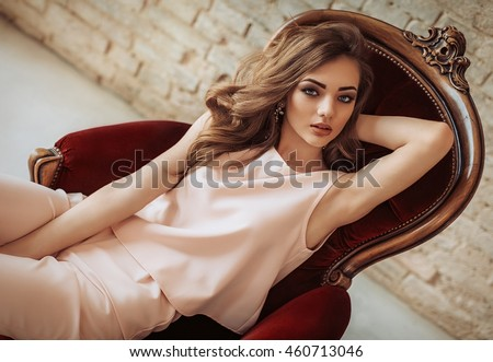 Portrait of beautiful young woman with makeup in fashion clothes - stock photo