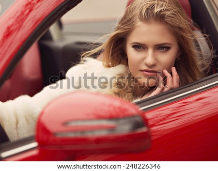 Portrait of beautiful young woman with makeup in fashion clothes in car - stock photo