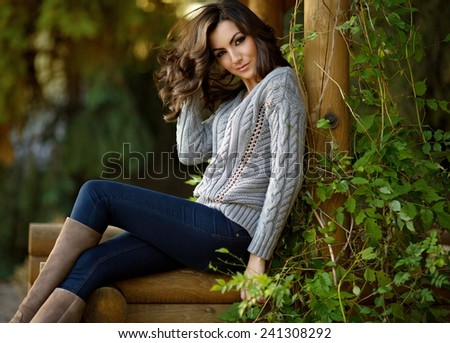 Portrait of beautiful young woman with makeup in fashion clothes on hature - stock photo