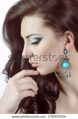 Portrait of beautiful young woman with makeup with jewelry - stock photo