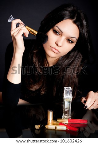 Portrait of beautiful young woman with perfume bottles and red gloss lips - stock photo