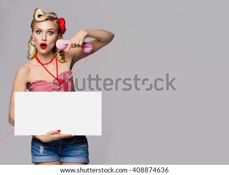 Portrait of beautiful young woman with phone and blank signboard, dressed in pin-up style. Caucasian blond model posing in retro fashion and vintage concept studio shoot, on grey background.