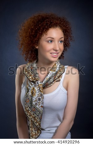 portrait of beautiful young woman with red curly hair and blue eyes in white shirt with a scarf, studio shooting, on dark blue background - stock photo