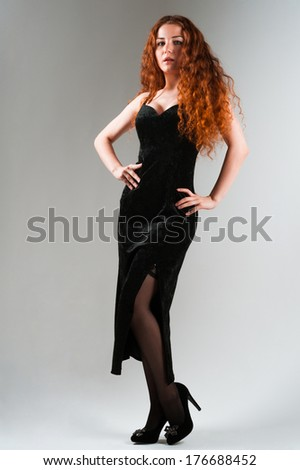 Portrait of Beautiful young woman with red hairs in black dress standing on grey background full length