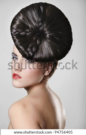 Portrait of beautiful young woman with red lips and unusual hair style  on gray background - stock photo