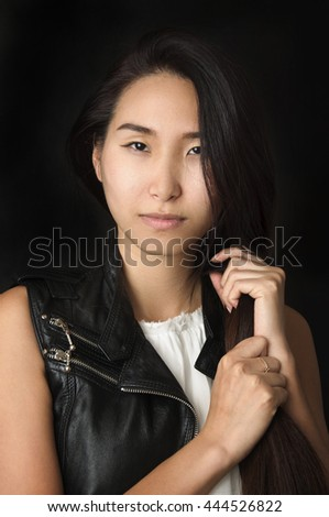 Portrait of beautiful young woman with serious look on black background