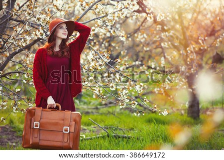 portrait of beautiful young woman with suitcase and hat near blooming tree - stock photo