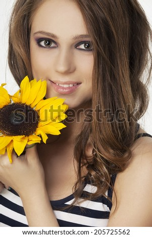 Portrait of beautiful young woman with sunflower and brown hair - stock photo