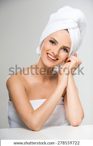 Portrait of beautiful young woman with towel on head in spa salon. - stock photo