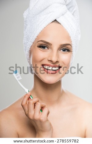 Portrait of beautiful young woman with towel on head using toothbrush. - stock photo