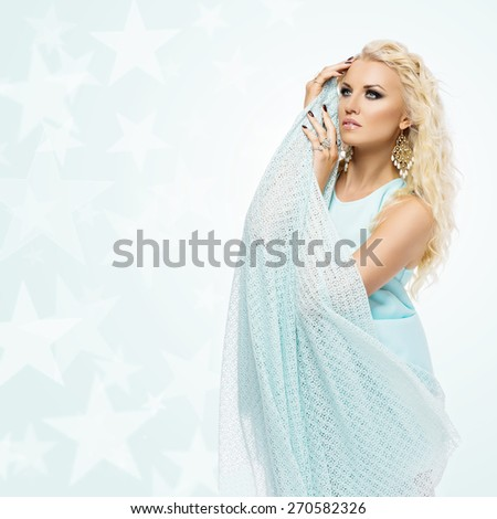 Portrait of beautiful young woman with wavy long blond hair and bright makeup wearing blue dress. Isolated. Copy space - stock photo