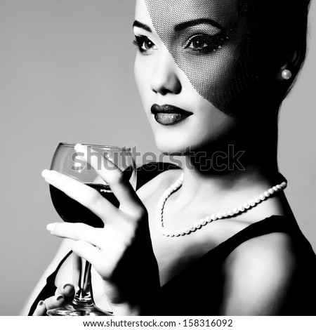 Portrait of beautiful young woman with wine glass black and white retro stylization