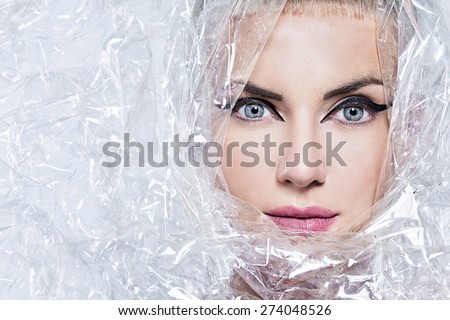 Portrait of beautiful young woman, wrapped in cellophane