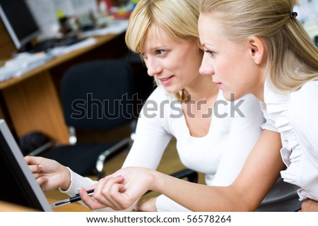 Portrait of beautiful young women working together in the office of the computers - stock photo