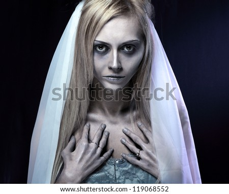 Portrait of beautiful zombie corpse bride looked scary and standing at dark background. shot in studio - stock photo