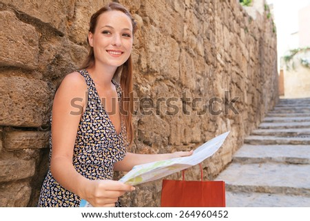 Portrait of beauty tourist woman visiting a destination city leaning on old textured stone wall in a street with steps, using a map, sightseeing on holiday. Travel and shopping on vacation, outdoors. - stock photo