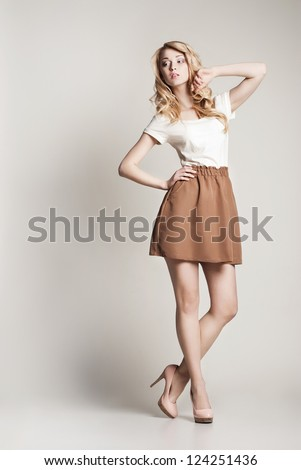 Portrait of beautyful posing blond woman with long curly hair on white background - stock photo