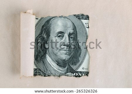 Portrait of Benjamin Franklin, is depicted on the banknote one hundred dollars USA peeking through broken old sheet of paper - stock photo
