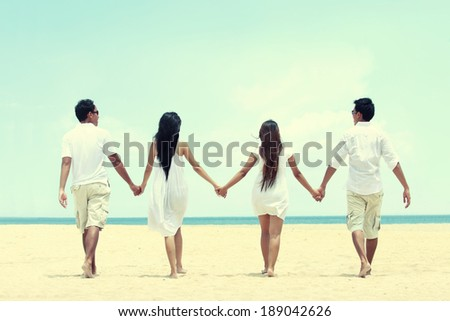 Portrait of best friend in white walking together holding each other hand - stock photo