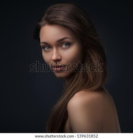 Portrait of beutiful girl isolated on dark background - stock photo