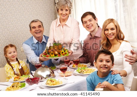 Portrait of big family sitting at festive table and looking at camera with smiles - stock photo