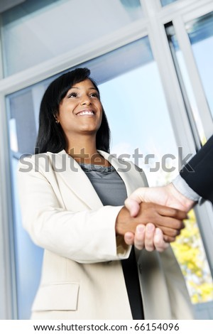 Portrait of black business woman shaking hands - stock photo