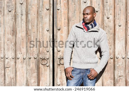 Portrait of black man wearing casual clothes in urban background - stock photo