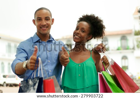Portrait of black tourist heterosexual couple in Casco Antiguo - Panama City with shopping bags. The man and his girlfriend smile at the camera doing ok sign - stock photo