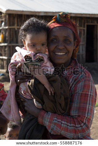 portrait of black woman carrying her child, december 2015, oromia state, ethiopia
