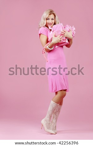 Portrait of blond beautiful girl with gifts on pink background
