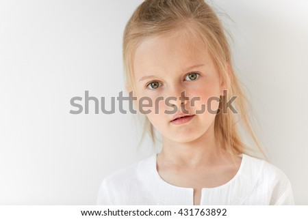 Portrait of blond child with pony-tail and white clothes. Nice little girl looking at camera with slightly open mouth and big green eyes. Child innocence and infant beauty is so natural. - stock photo