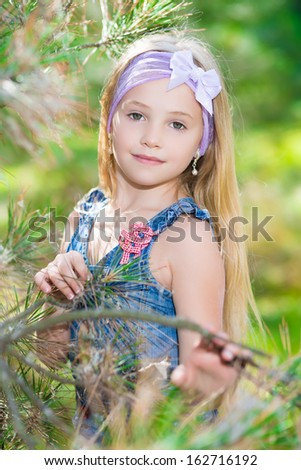 Portrait of blond girl posing in pine branches