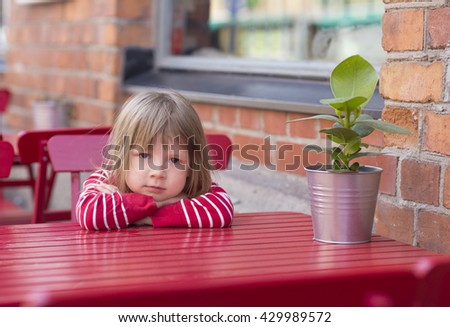 portrait of blond in red shirt girl in children garden age sitting at table and waiting for food in cafe outdoors - stock photo