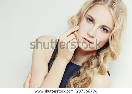 Portrait of blond slim woman on light background - stock photo