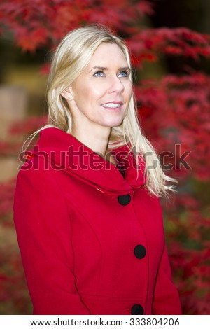 portrait of blond woman in a red coat in front of a tree in autumn - stock photo