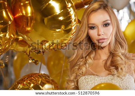 portrait of blond young woman between golden balloons and ribbons with a sweet smile