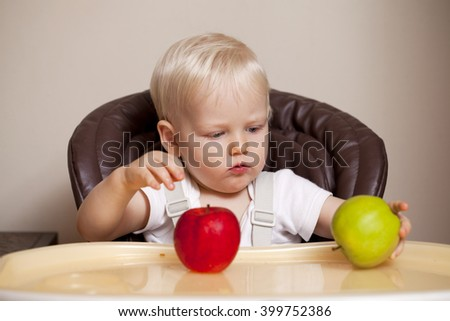Portrait of blonde baby boy sitting at the dinner table - stock photo