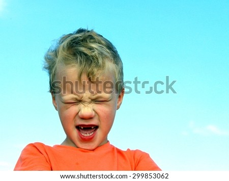 portrait of blonde boy with frowning face outdoor - stock photo