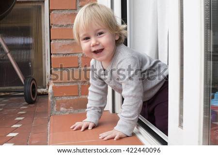 portrait of blonde caucasian baby nineteen month age chubby face looking at camera peering terrace floor supported on her arms - stock photo