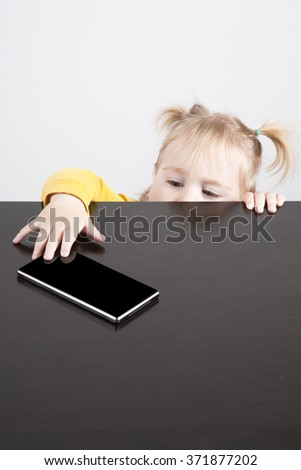 portrait of blonde caucasian baby nineteen month age chubby face yellow shirt trying to take mobile phone smartphone with her hand - stock photo