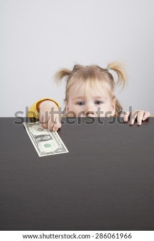 portrait of blonde caucasian baby nineteen month age with pigtails chubby face yellow shirt looking at camera and taking a dollar banknote on brown table - stock photo